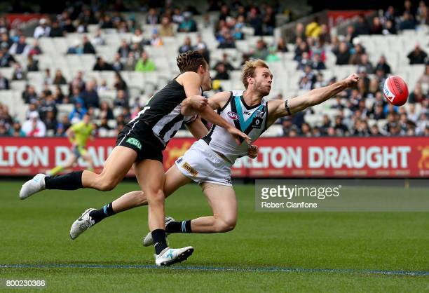 Jack Hombsch of the Power punches the ball away from Darcy Moore of the Magpies during the round 14 AFL match between the Collingwood Magpies and the...