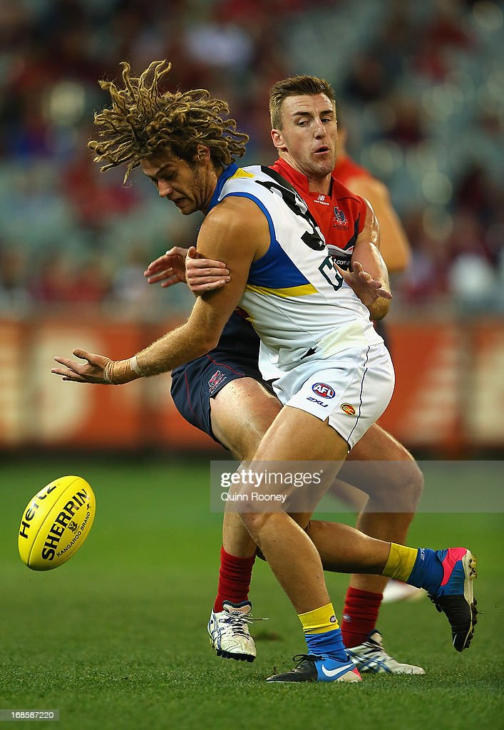 Jack Hutchins of the Suns is tackled by Lynden Dunn of the Demons during the round seven AFL match between the Melbourne Demons and the Gold Coast Suns at Melbourne Cricket Ground on May 12, 2013 in Melbourne, Australia.