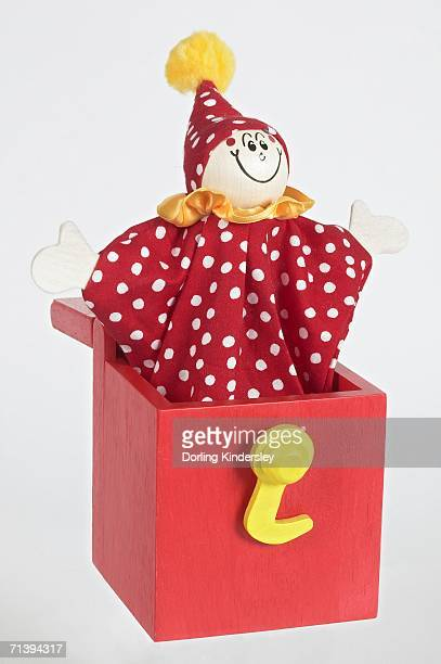 'Jack in a box', smiling clown puppet popping out of red wooden box with arms extended to sides, front view.