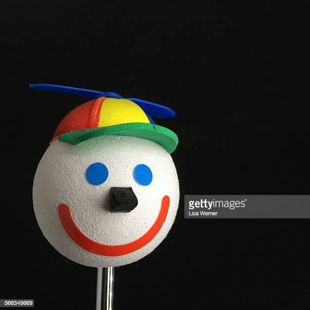 A 'Jack in the Box' smiling happy face car antenna ball topper with a spinning baseball cap