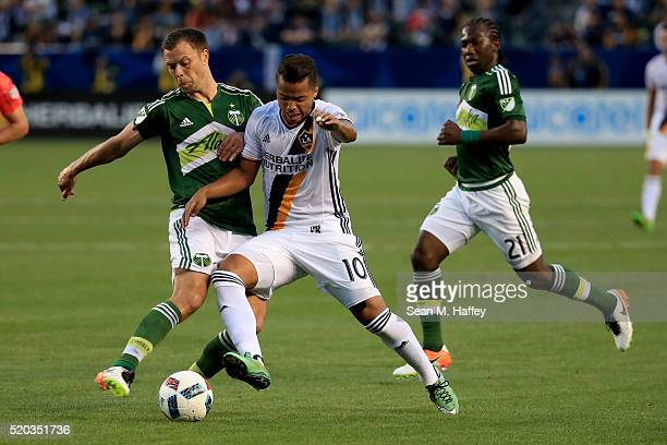 Jack Jewsbury and Ned Grabavoy of Portland Timbers battle Giovani dos Santos of Los Angeles Galaxy for a loose ball during the first half of their...