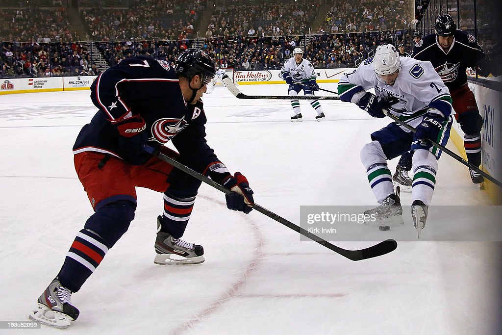 Jack Johnson #7 of the Columbus Blue Jackets and <a gi-track='captionPersonalityLinkClicked' href=/galleries/search?phrase=Dan+Hamhuis&family=editorial&specificpeople=204213 ng-click='$event.stopPropagation()'>Dan Hamhuis</a> #2 of the Vancouver Canucks battle for control of a loose puck during the first period on March 12, 2013 at Nationwide Arena in Columbus, Ohio.