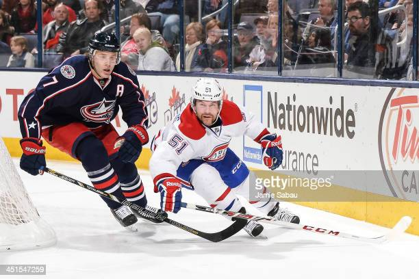 Jack Johnson of the Columbus Blue Jackets and David Desharnais of the Montreal Canadiens chase after a loose puck on November 15 2013 at Nationwide...