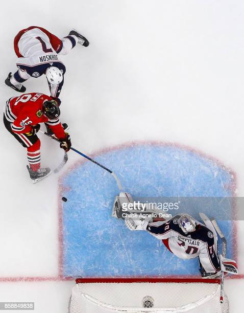Jack Johnson of the Columbus Blue Jackets and Jonathan Toews of the Chicago Blackhawks battle for the puck next to goalie Joonas Korpisalo at the...