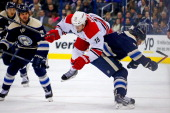 Jack Johnson of the Columbus Blue Jackets checks Tuomu Ruutu of the Carolina Hurricanes during the first period on January 10 2014 at Nationwide...