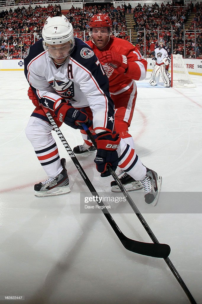 Jack Johnson of the Columbus Blue Jackets controls the puck in front of Dan Cleary of the Detroit Red Wings during a NHL game at Joe Louis Arena on...