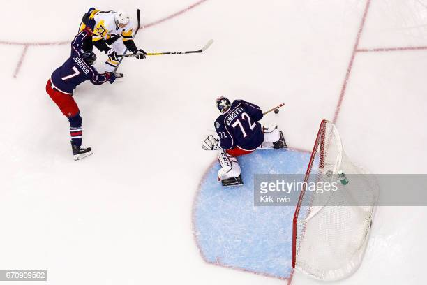 Jack Johnson of the Columbus Blue Jackets falls back on defense as Sergei Bobrovsky of the Columbus Blue Jackets stops a shot from Evgeni Malkin of...