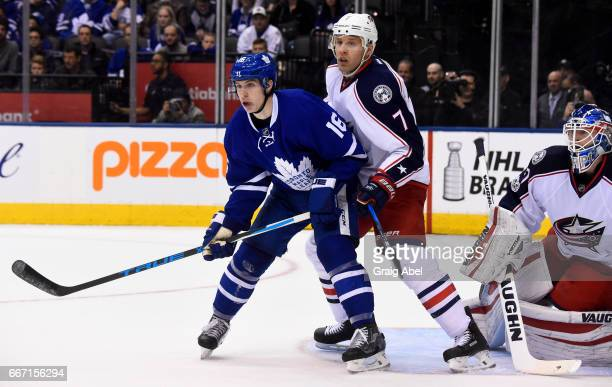 Jack Johnson of the Columbus Blue Jackets tries to clear Mitch Marner of the Toronto Maple Leafs from the crease of Joonas Korpisalo of the Columbus...