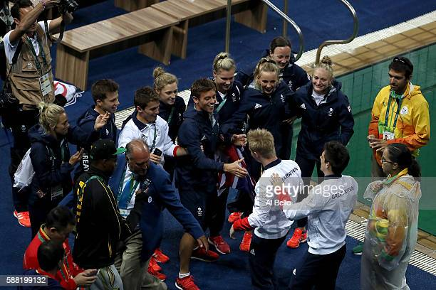 Jack Laugher and Chris Mears of Great Britain celebrate winning gold with their team members in the Men's Diving Synchronised 3m Springboard Final on...