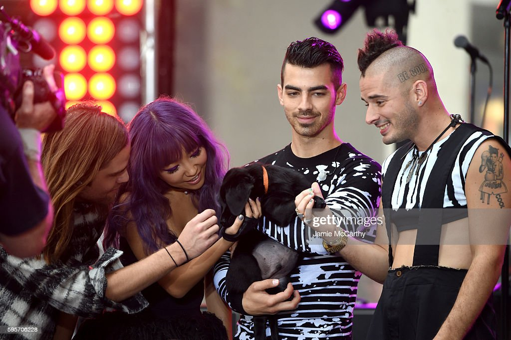 Jack Lawless JinJoo Lee Joe Jonas and Cole Whittle of the band DNCE pose on stage with the dog on NBC's 'Today' at Rockefeller Plaza on August 26...