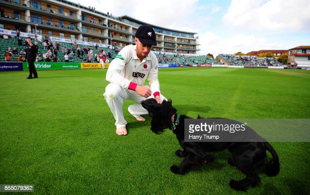 Jack Leach of Somerset celebrates victory with a pet dog during Day Four of the Specsavers County Championship Division One match between Somerset...