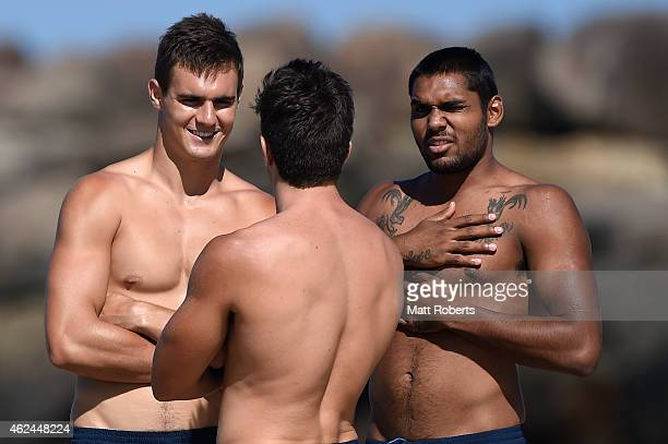 Jack Leslie and Timmy Sumner speak with team mate Jesse Lonergan during a Gold Coast Suns AFL preseason training session at Casuarina Beach on...