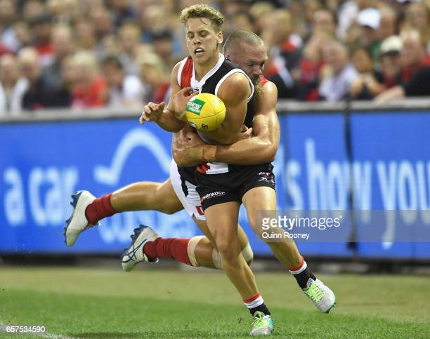Jack Lonie of the Saints handballs whilst being tackled by Max Gawn of the Demons during the round one AFL match between the St Kilda Saints and the...