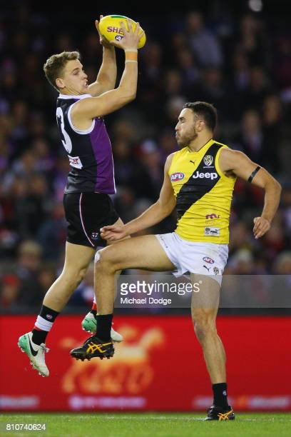Jack Lonie of the Saints marks the ball against Shane Edwards of the Tigers during the round 16 AFL match between the St Kilda Saints and the...