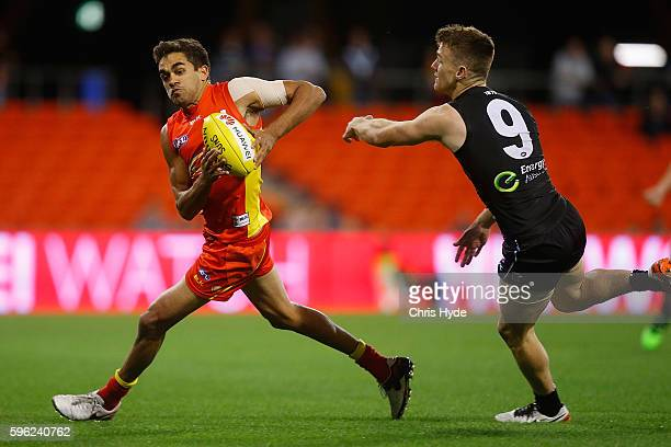 Jack Martin of the Suns runs the ball during the round 23 AFL match between the Gold Coast Suns and the Port Adelaide Power at Metricon Stadium on...