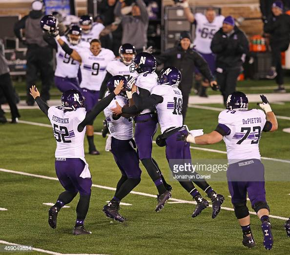 Jack Mitchell of the Northwestern Wildcats is lifted by Garrett Dickerson and Christian Salem after kicking the gamewinning field goal against the...