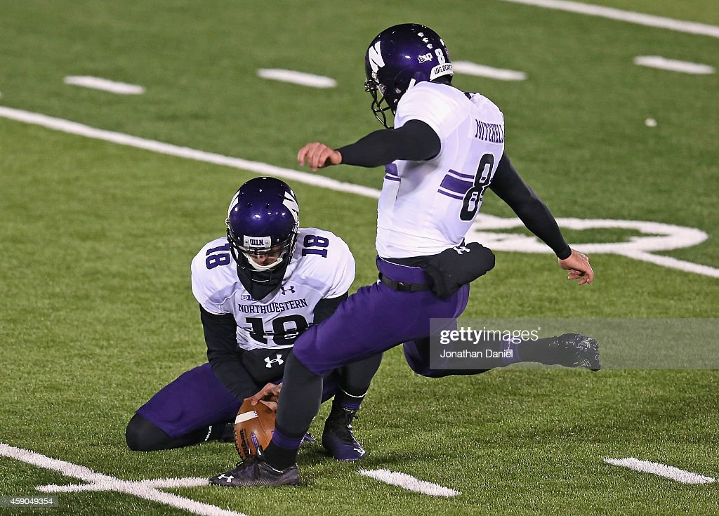 Jack Mitchell of the Northwestern Wildcats kicks the gamewinning field goal out of the hold of Christian Salem against the Notre Dame Fighting Irish...