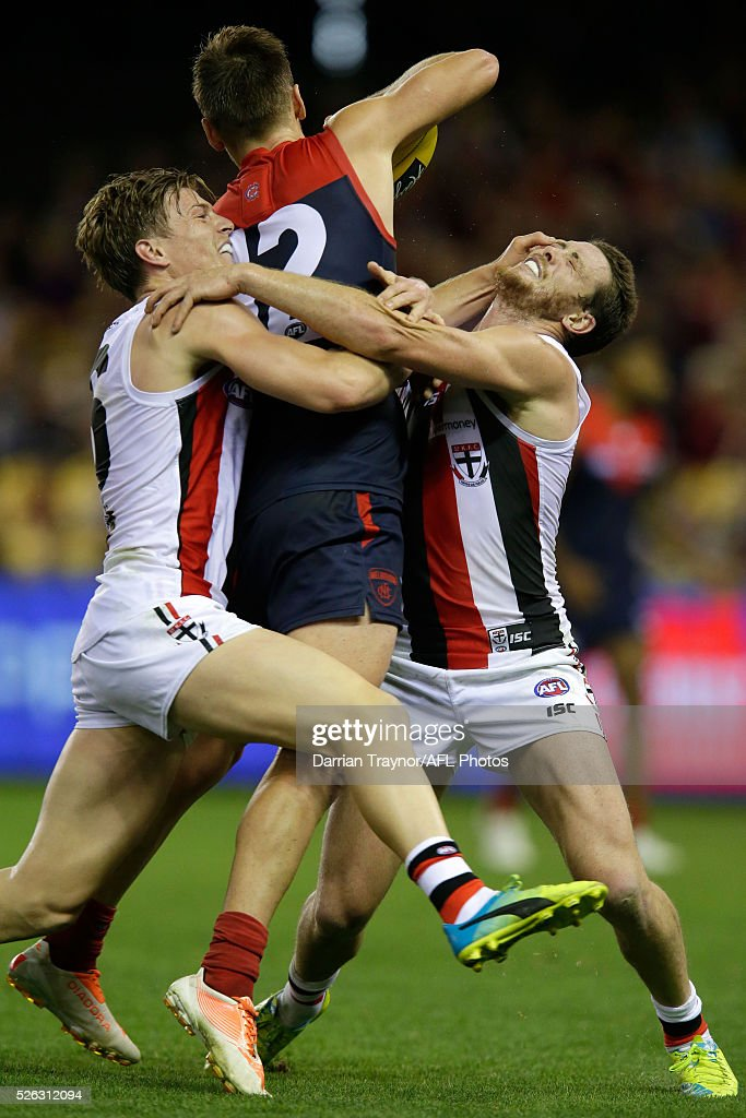 Jack Newnes and Jack Steven of the Saints tackles Dom Tyson of the Demons during the round six AFL match between the Melbourne Demons and the St Kilda Saints at Etihad Stadium on April 30, 2016 in Melbourne, Australia.