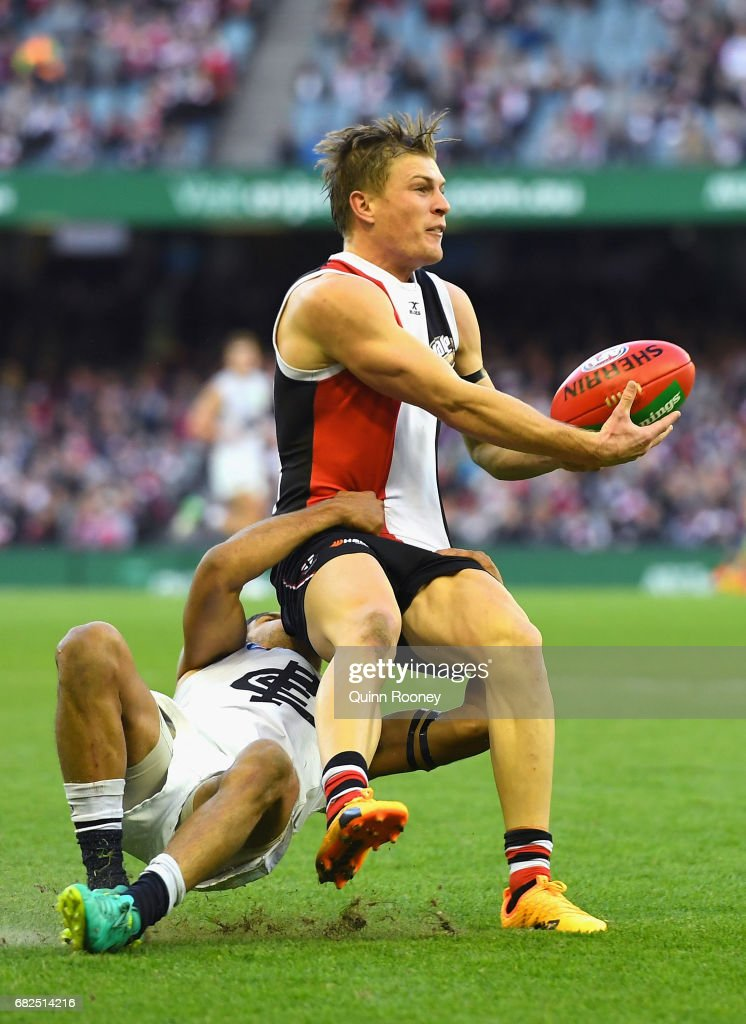 Jack Newnes of the Saints handballs whilst being tackled by Sam Petrevski-Seton of the Blues during the round eight AFL match between the St Kilda Saints and the Carlton Blues at Etihad Stadium on May 13, 2017 in Melbourne, Australia.