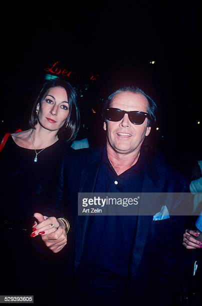 Jack Nicholson with Anjelica Huston both in black holding hands circa 1970 New York