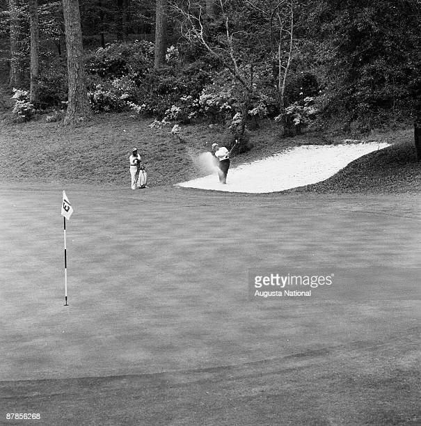 Jack Nickalus hits out of a bunker while his caddie watches on the 13th green during the 1965 Masters Tournament at Augusta National Golf Club in...