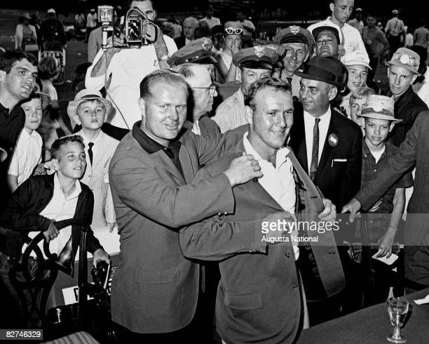 Jack Nicklaus presents Arnold Palmer with the green jacket during the Presentation Ceremony at the 1964 Masters Tournament at Augusta National Golf...