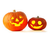 Two Jack O Lantern halloween pumpkins with candle light inside isolated on white background