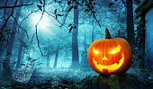 Glowing Jack o lantern in a creepy old overgrown cemetery with cool blue moonlight