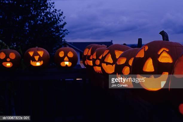 Jack o' lanterns in row on railing, dusk