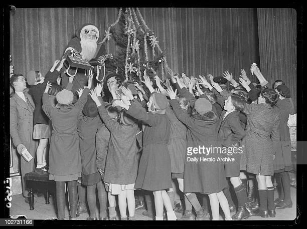 Jack Payne as Father Christmas Holborn Empire London 1934 Children reach for presents handed out