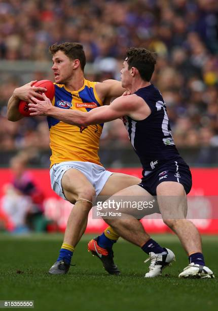 Jack Redden of the Eagles gets tackled by Lachie Neale of the Dockers during the round 17 AFL match between the Fremantle Dockers and the West Coast...