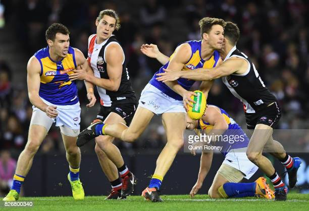 Jack Redden of the Eagles handballs whilst being tackled by Koby Stevens of the Saints during the round 20 AFL match between the St Kilda Saints and...
