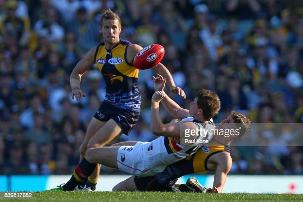 Jack Redden of the Eagles tackles Matt Crouch of the Crows during the round 23 AFL match between the West Coast Eagles and the Adelaide Crows at...