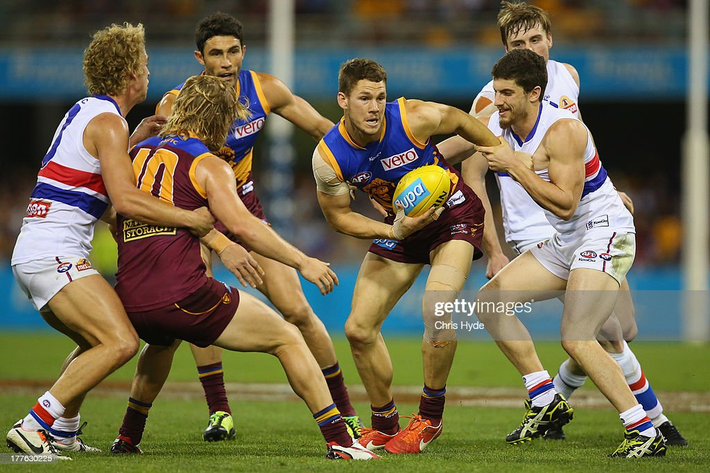 Jack Redden of the Lions is tackled by Tom Liberatore of the Bulldogs during the round 22 AFL match between the Brisbane Lions and the Western Bulldogs at The Gabba on August 25, 2013 in Brisbane, Australia.