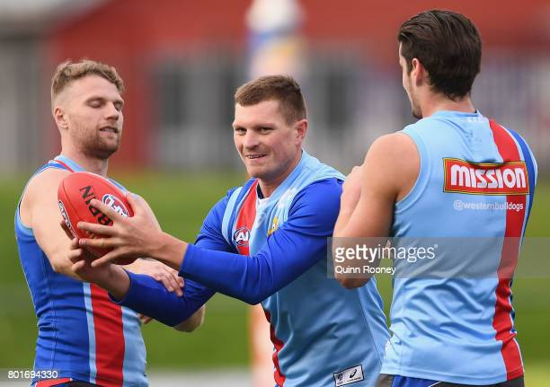 Jack Redpath of the Bulldogs marks inbetween Jake Stringer and Tom Boyd during a Western Bulldogs AFL training session at Whitten Oval on June 27...