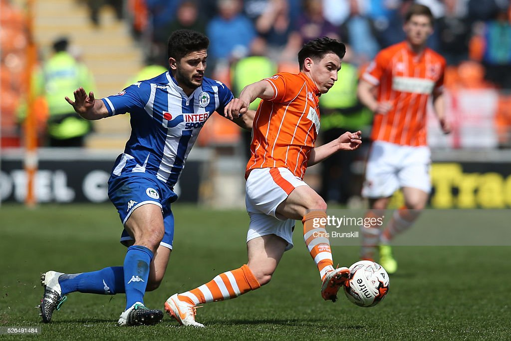 Jack Redshaw of Blackpool evades Sam Morsy of Wigan Athletic during the Sky Bet League One match between Blackpool and Wigan Athletic at Bloomfield Road on April 30, 2016 in Blackpool, England.