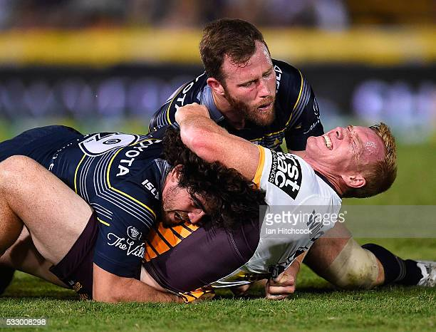 Jack Reed of the Broncos is tackled by Gavin Cooper and Jake Granville of the Cowboys during the round 11 NRL match between the North Queensland...