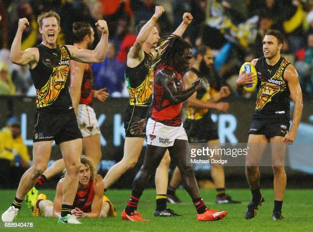 Jack Riewoldt and Shane Edwards of the Tigers celebrates the win on the final siren as Dyson Heppell of the Bombers and Anthony McDonaldTipungwuti of...