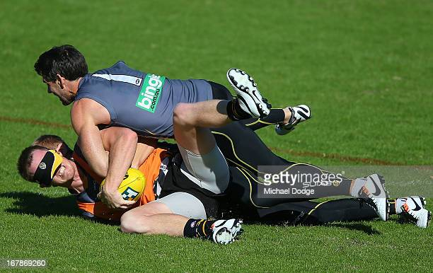Jack Riewoldt gets tackled by David Astbury and Chris Newman during a Richmond Tigers AFL training session at ME Bank Centre on May 2 2013 in...
