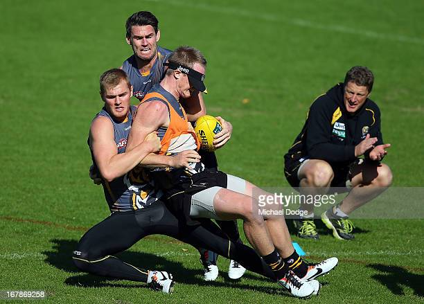 Jack Riewoldt gets tackled by David Astbury and Chris Newman much to the delight of coach Damien Hardwick during a Richmond Tigers AFL training...
