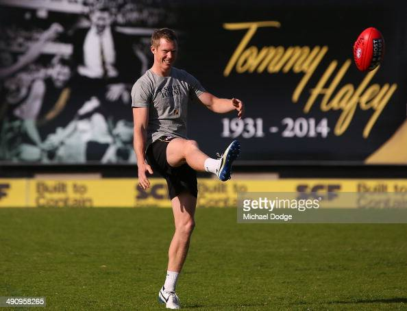 Jack Riewoldt kicks the ball in front of the billboard in honour of the late Tom Hafey during a Richmond Tigers AFL training session at ME Bank...