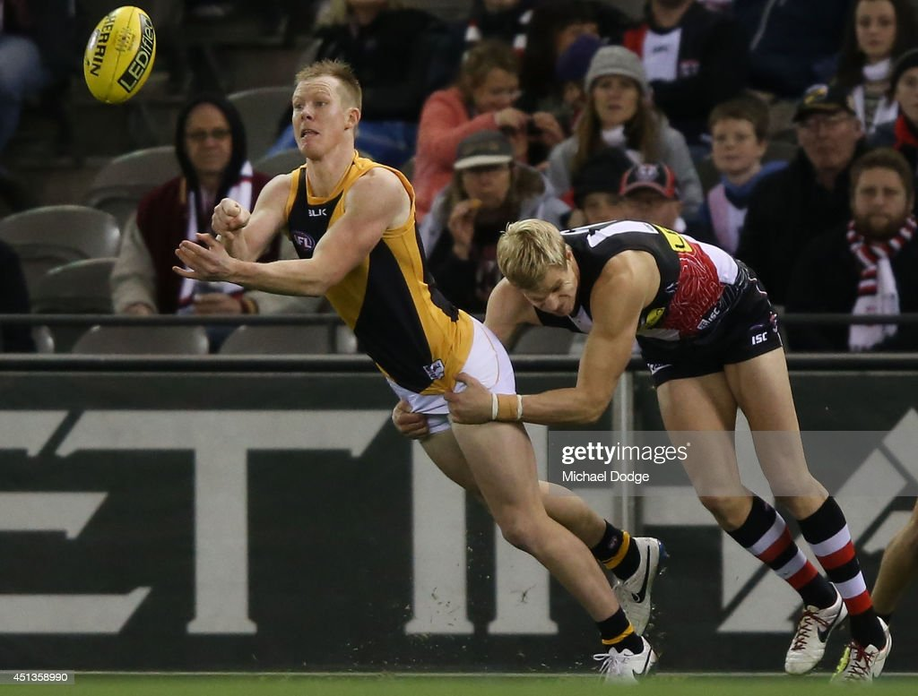 Jack Riewoldt of the Tigers handballs away from his cousin Nick Riewoldt of the Saints during the round 15 AFL match between the St Kilda Saints and...