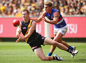 Jack Riewoldt of the Tigers handballs whilst being tackled by Michael Talia of the Bulldogs during the round two AFL match between the Richmond...