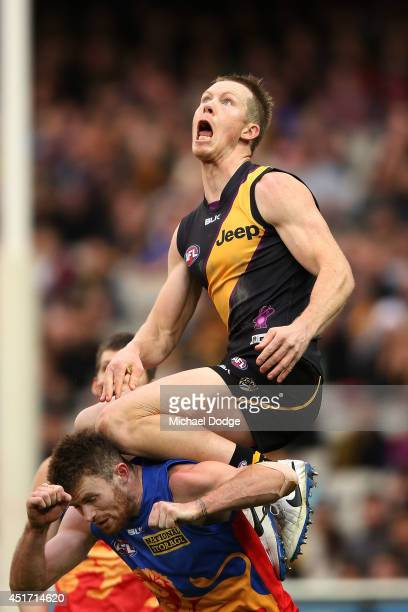 Jack Riewoldt of the Tigers jumps for an attempted high mark over Pearce Hanley of the Lions during the round 16 AFL match between the Richmond...