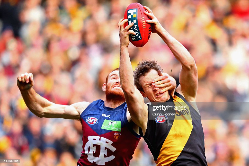 Jack Riewoldt of the Tigers marks infront of Daniel Merrett of the Lions during the round 14 AFL match between the Richmond Tigers and the Brisbane...
