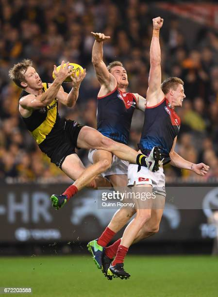 Jack Riewoldt of the Tigers marks over the top of Tom McDonald and Sam Frost of the Demons during the round five AFL match between the Richmond...