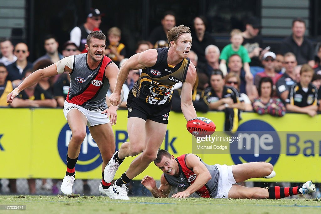 Jack Riewoldt of the Tigers runs with the ball away from Tayte Pears (L) and <a gi-track='captionPersonalityLinkClicked' href=/galleries/search?phrase=Brent+Stanton&family=editorial&specificpeople=234867 ng-click='$event.stopPropagation()'>Brent Stanton</a> of the Bombers during an AFL Practice Match between the Richmond Tigers and the Essendon Bombers at Punt Road Oval on March 7, 2014 in Melbourne, Australia.