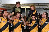 Jack Riewoldt of the Tigers sings the club song with team mates while carrying Tigers junior mascot Nate Anderson on his shoulders after winning the...