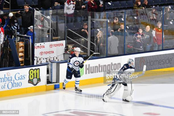 Jack Roslovic and goaltender Eric Comrie of the Winnipeg Jets take the ice for pregame warmups prior to a game against the Columbus Blue Jackets on...
