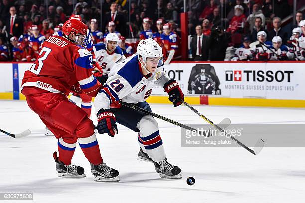 Jack Roslovic of Team United States skates the puck against Mikhail Sidorov of Team Russia during the 2017 IIHF World Junior Championship semifinal...